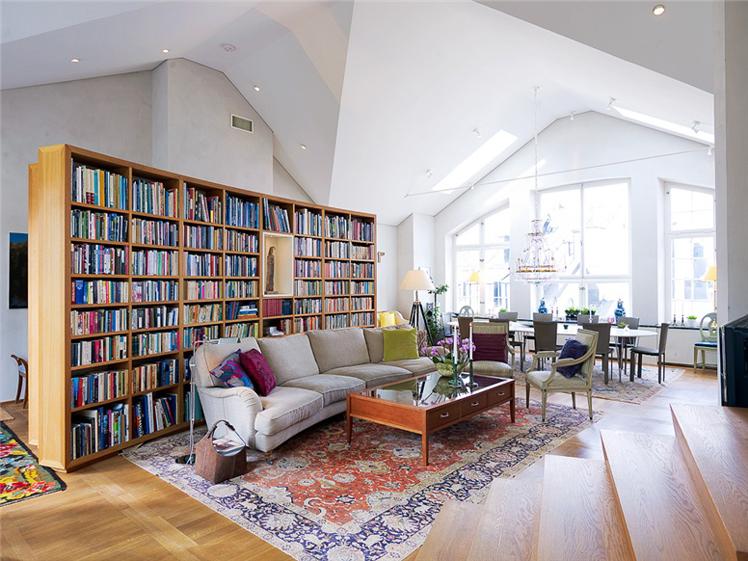 Vindsvåning i Stockholm av Rex Arkitektbyrå. Platsbyggd bokhylla i vardagsrummet.