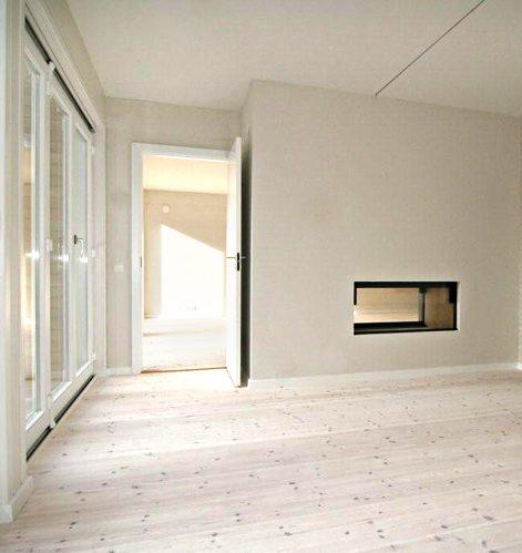 Vardagsrum med eldstad i det nya parhuset i massivträ av Rex Arkitektbyrå